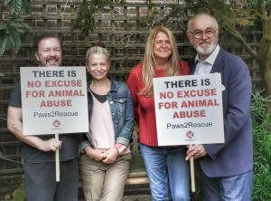 Ricky Gervais with wife Jane Fallon and Peter Egan holding bespoke protest placards for animal rights